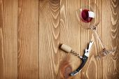 Red wine glass, corkscrew and wine cork on wooden table background with copy space