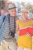 Happy tourist couple using guide book in the city on a sunny day