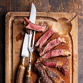 picture of ribeye steak  - Medium rare Beef steak Ribeye with knife and fork for meat on cutting board on dark wooden background - JPG