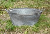 picture of washtub  - Empty tin bath standing on rough grass and weeds - JPG