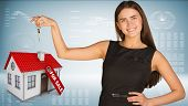 Beautiful woman with keys and small house