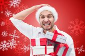 Festive man holding christmas gifts against red snow flake pattern design