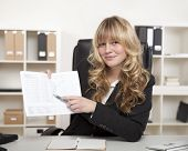 Smiling Businesswoman Pointing To A Spreadsheet