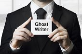 image of politician  - businessman in black suit holding sign ghost writer plagiarism - JPG