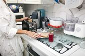 Midsection of senior woman preparing toast at kitchen counter