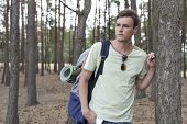 Handsome young man with backpack hiking in woods