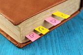 Book with bookmarks on color wooden background