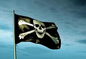 stock photo of skull crossbones flag  - Pirate skull and crossbones flag waving in the evening - JPG