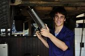 stock photo of car repair shop  - happy car mechanic working at the car repair shop - JPG