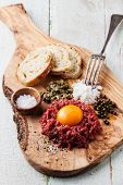 Beef Tartare With Capers And Fresh Onion On Olive Wood Board