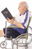 handicap senior in wheelchair reading the bible vertical