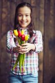 Bunch of fresh red and yellow tulips held by little girl