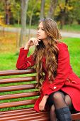 Young woman dressed in red coat sitting in autumn park on a bench.