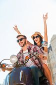 picture of vespa  - Beautiful young couple riding scooter together while happy woman raising arms and smiling - JPG