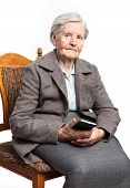 Senior woman sitting on chair and holding phone