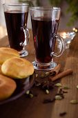 Mulled wine with spices and ginger rolls on a Christmas table