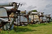 pic of lineup  - The posterior view of a lineup of old threshing machines finds a blower pipe resting atop of the frame on each piece of equipment - JPG