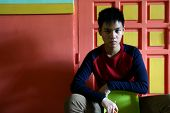 Young Teen Sitting on a Chair Against a colorful wall