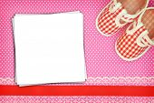 Baby shoes and blank cards on polka dots background