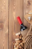Red wine bottle, corks and corkscrew on wooden table background with copy space