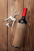 Red wine bottle and corkscrew on wooden table background. Top view