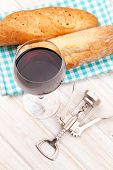 Red wine, bread and corkscrew on white wooden table background