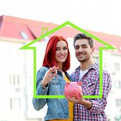 Loving couple with keys and piggy bank in drawing house