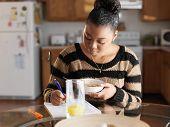 teen girl eating and doing homework at breakfast