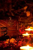 Magic chest on dry grasses by candlelight