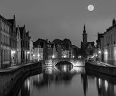 European medieval night city view background - Bruges (Brugge) canal in the evening, Belgium. Black and white version