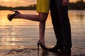 legs of couple near the water at sunset