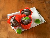 three chocolate muffins in red paper baskets, on the wooden table with fabric linen