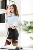 stock photo of short skirt  - Pretty young business woman in a short skirt standing in front of shelves with binders and with a smile looking at the camera - JPG