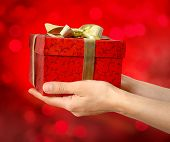 hand holding red gift box with ribbon