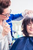 foto of hairspray  - Female coiffeur giving women hairstyling with hairspray in hairdresser shop - JPG