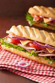 long baguette sandwich with ham cheese tomato and lettuce