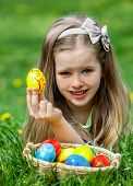 Happy child find easter egg outdoor. Girl lying on green grass