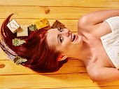 Young woman in sauna with soap. Girl lying on wooden boards