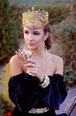 pic of queen crown  - Elegant young woman dressed like queen with a crown holding an apple - JPG