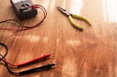 A wooden work desk with an electric circuit tester, and a needle nose pliers. Focus is on foreground.