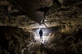 Cave with light and man exploring
