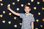 Boy Attaching Heart On Dark Background