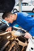 Mechanic examining under hood of car with torch at the repair garage