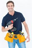 Portrait of happy carpenter holding portable drill machine over white background