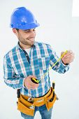 Happy carpenter looking at measure tape while standing against white background