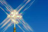 Golden Orthodox Cross Against Blue Sky Background