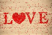 Love spelled out in petals against bleached wooden planks background
