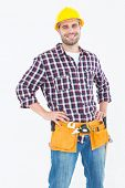 Portrait of happy handyman wearing tool belt while standing hands on hips over white background