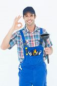 Portrait of plumber holding plunger while gesturing OK sign over white background
