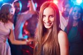 Cheerful girl looking at camera on background of her friends dancing